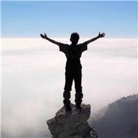 一个人张开双手站在山顶上的岩石上的照片